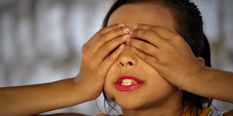 Child with her eyes covered by her hands