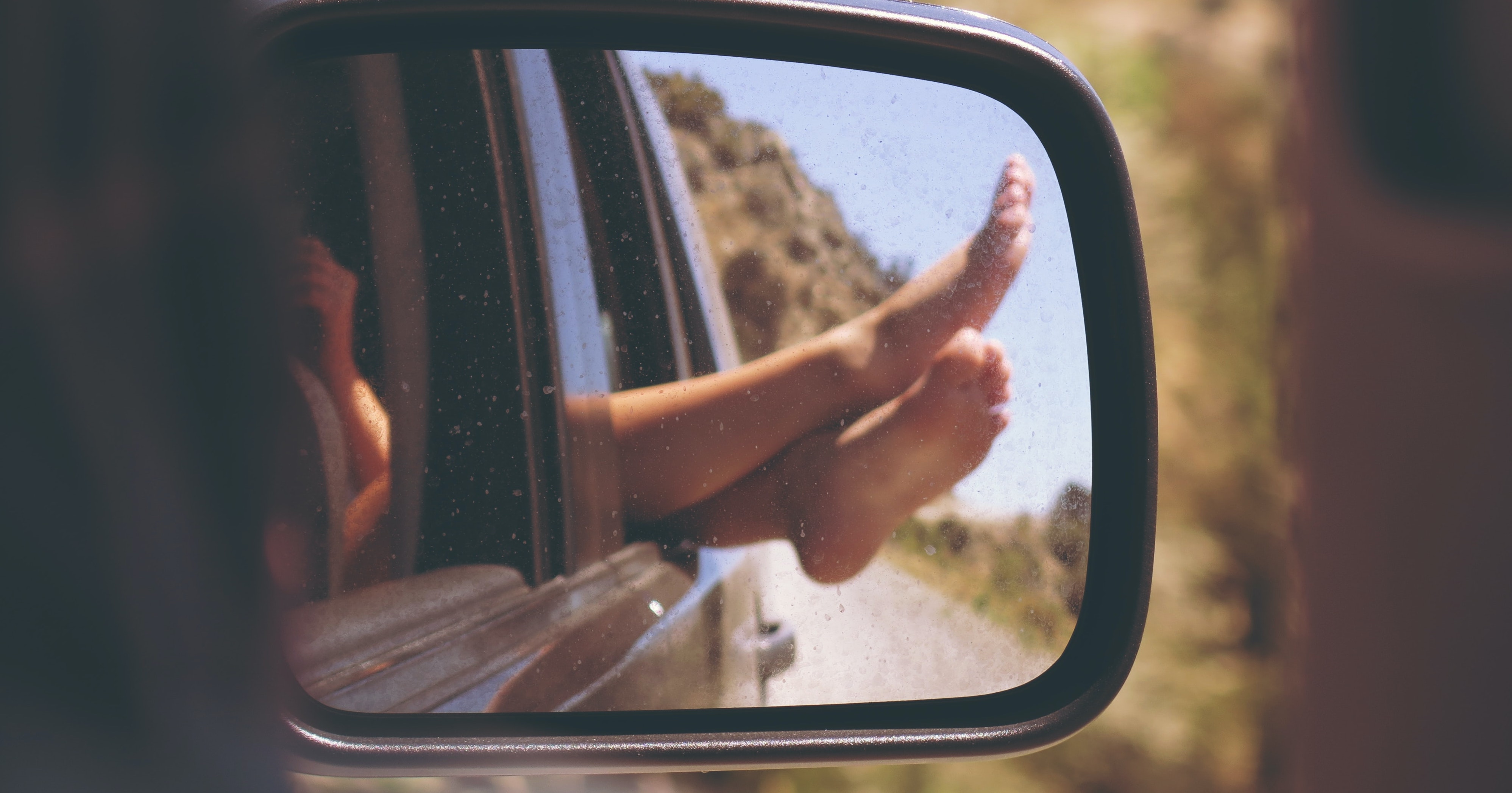 Feet out the window and car wing mirror