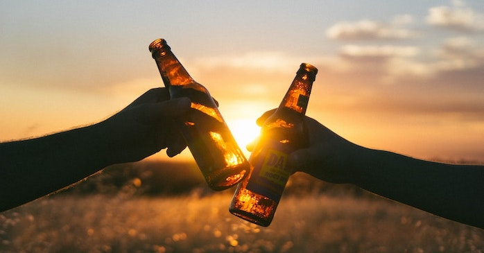 Two beer bottle clinking in the sunset